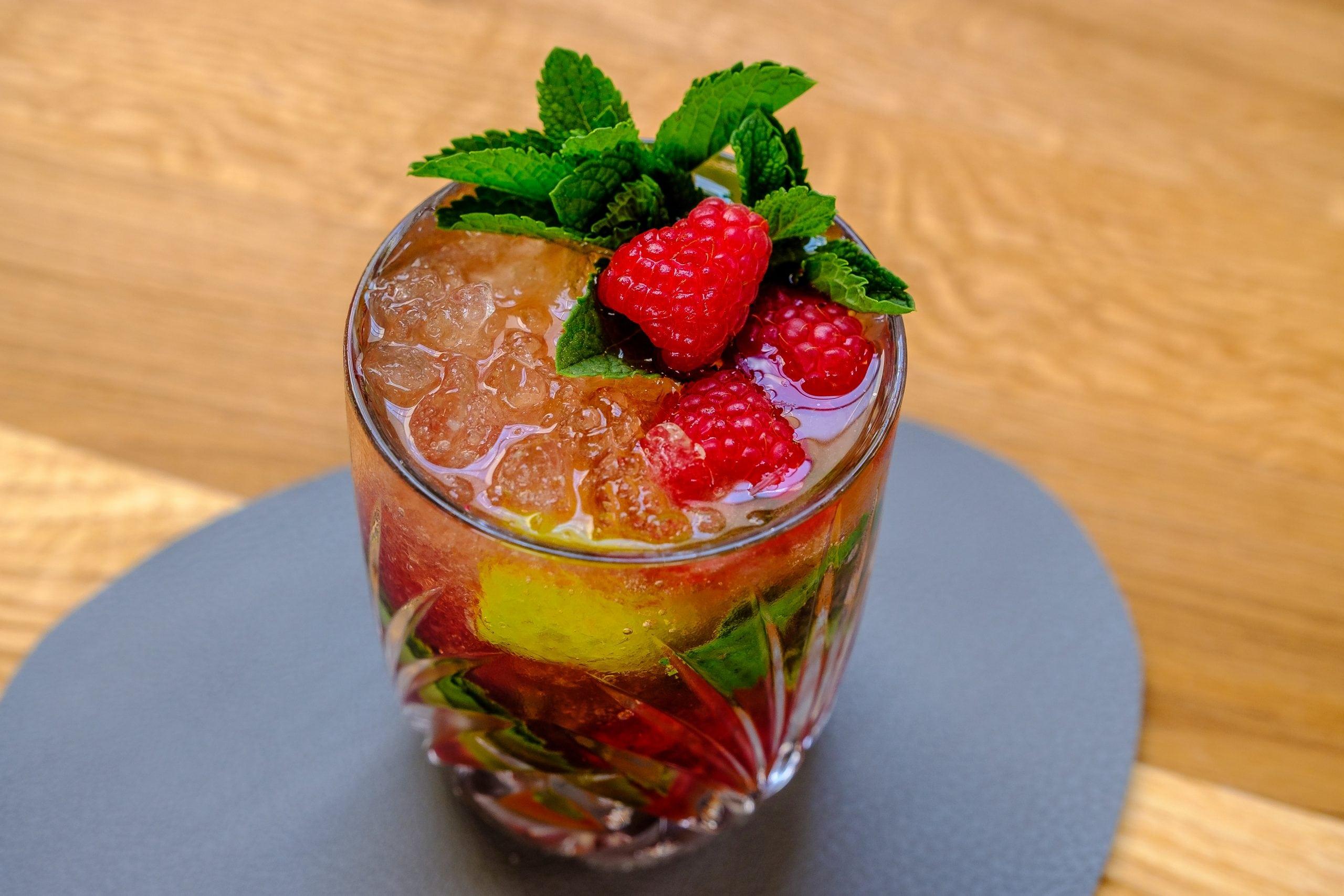 Cocktail dekoriert mit Himbeeren und Minze