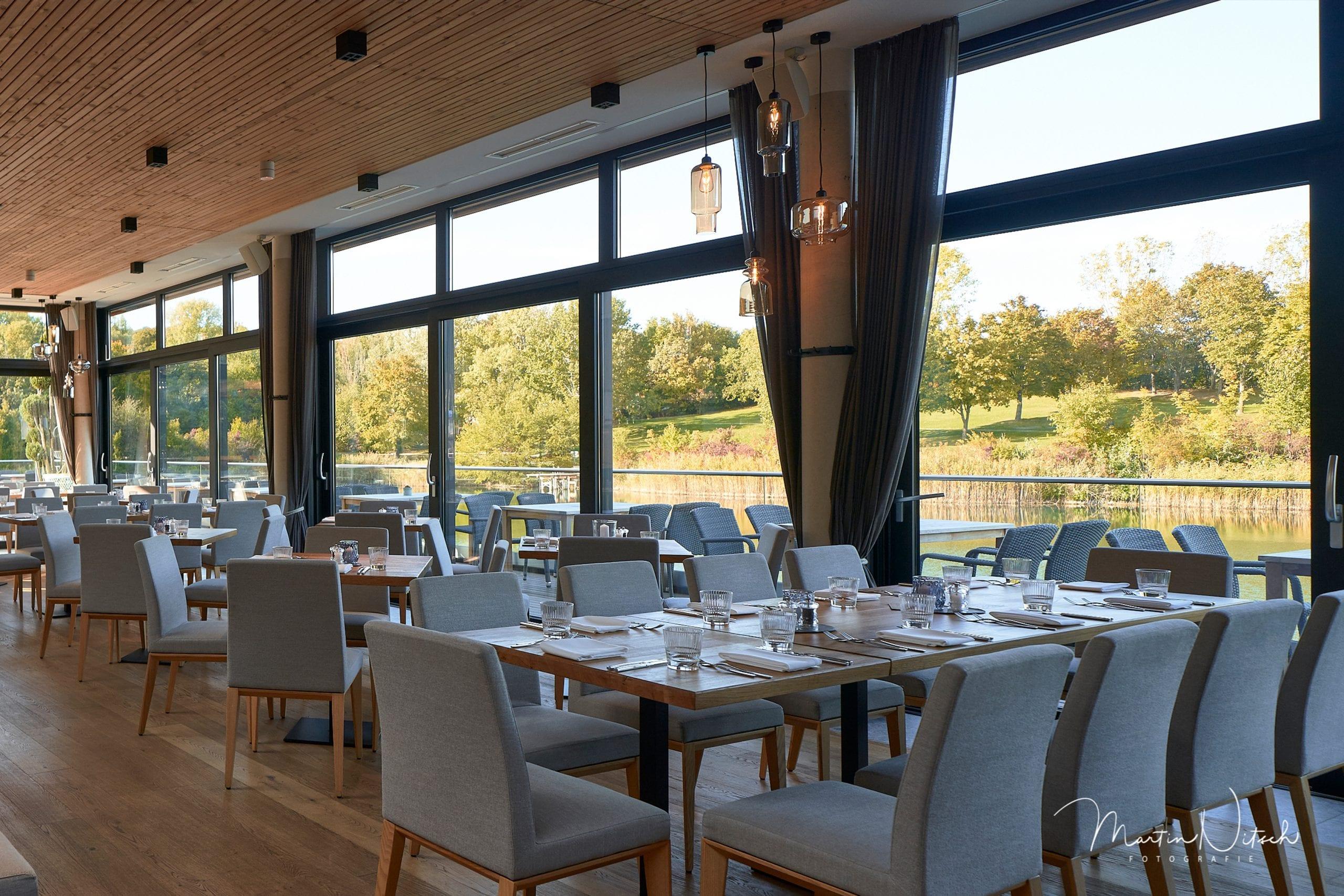 Gedeckte Tische im Innenbereich mit Blick auf den Teich